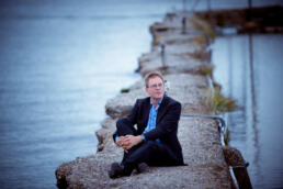 Header image of Theo Verbey, sitting on a concrete walkway with water on both sides